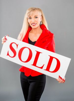 Realtor Holding Sold Sign Used For Promotional Purposes.jpg